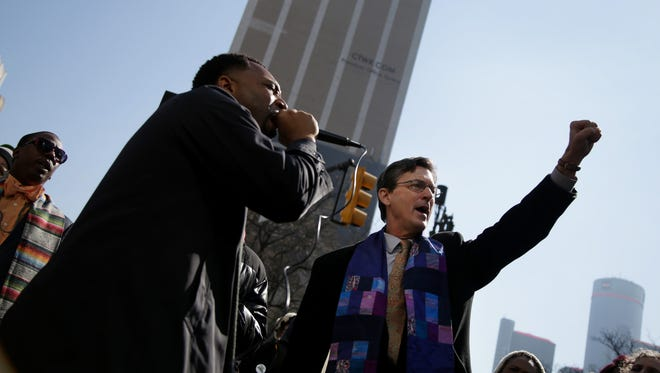 Rev. Jawanza Colvin of Olivet Institutional Baptist Church in Cleveland, left and Pastor John Lentz of Cleveland lead the crowd in chant in front of Quicken Loans headquarters in Detroit on Tuesday, March 21, 2017.