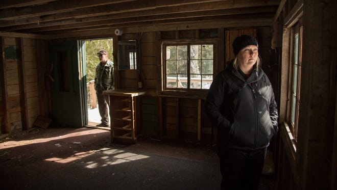 Kristin Ojaniemi, 34, looks out the window of her family's camp as her dad, Armas Ojaniemi, 60, of Bruce Crossing, stands in the doorway.