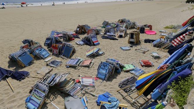 Beach chairs and umbrellas are piled on the beach near Allenhurst Beach Club.