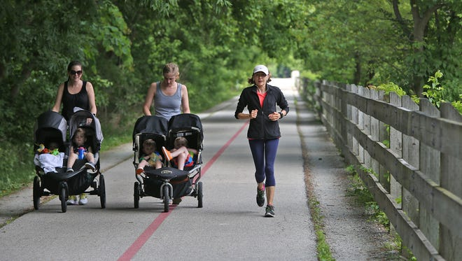 A woman passes two women who are pushing children in strollers on the Monon Trail in a file photo. Many of Indianapolis' suburbs are growing at a faster rate than the city, fueled in part by millennials who are looking for bigger, more affordable homes and better schools that can accommodate growing families.