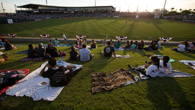 Fans sit on the Left-Field Berm at Whataburger Field before the start of the Hooks home opener against the Tulsa Drillers, Thursday, April 7, 2016.