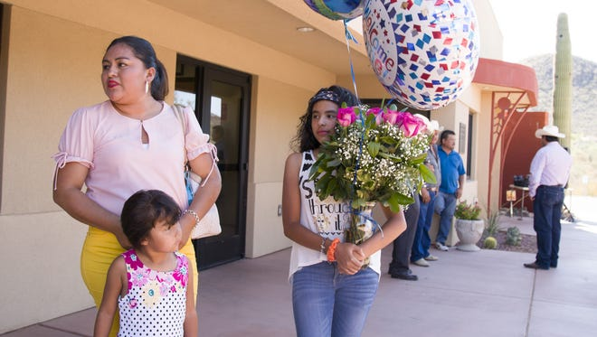Elia Vazques waits with her daughters, 14-year-old Jimena and 4-year-old Tatiana, to see her parents during the reunification at Our Lady of Fatima Parish in Tucson. It has been a decade since Vazques has seen them.
