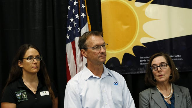 Traci Weaver of the U.S. Forest Service in Portland (left), Tyree Wilde of the National Weather Service and Gov. Kate Brown stand beside each other during an interagency press conference on the total solar eclipse at the Oregon State Fairgrounds in Salem, Oregon, on Tuesday, Aug. 15, 2017.