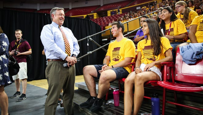 ASU President Michael Crow laughs alongside nursing freshman Nikkalaus Cheever before taking the stage during the freshman welcome rally at Wells Fargo Arena in Tempe on Aug. 15, 2017.