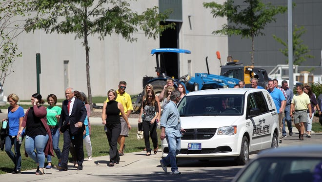 Employees make their way back to the City Services Center building in Cedar Rapids after an armed man, who was taken into custody, entered the building on Wednesday, Aug. 23, 2017.
