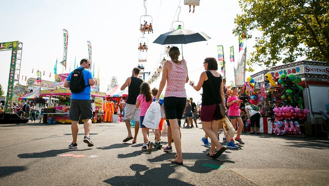 Heather Henningsen uses an umbrella to try and stay cool at the Oregon State Fair on Sunday, Sept. 3, 2017, in Salem, Ore. Henningsen said her family took several breaks in the shade and drank lots of water to avoid heat exhaustion.