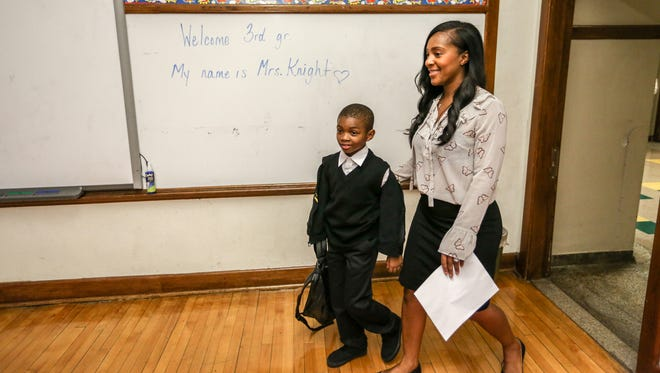 Tanesha Knight, 34, of Sterling Heights walks her new student  Ja'Kale Harris, 7, of Detroit to his desk, during the first day of school at Mary McLeod Bethune Elementary-Middle School in Detroit on Tuesday, Sept. 5, 2017.