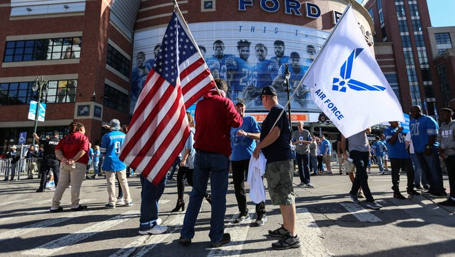 Protesters against NFL players taking a knee during the National Anthem march through Pride Plaza outside of Ford Field in Detroit for the Detroit Lions game against Carolina Panthers on Sunday, Oct. 8, 2017.