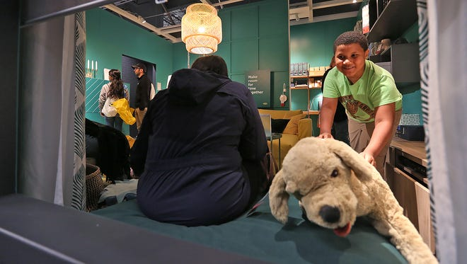 Liam Croney, right, grabs a quick hug from a display dog, at the IKEA Fishers grand opening, Wednesday, Oct. 11, 2017.
