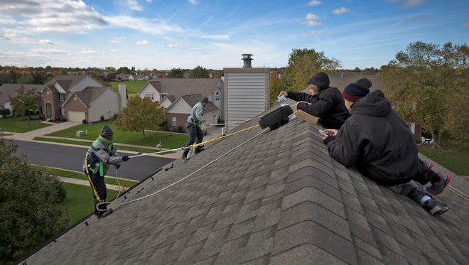 Members from Green Alternatives Inc. install a solar panel system in Carmel, Tuesday, October 31, 2017.