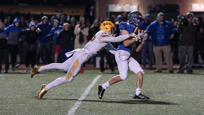 Utica Eisenhower's Ben Mats makes a catch behind Rochester Adams' Ben Luci during the second half at Swinehart Field in Utica, Friday, Nov. 3, 2017.