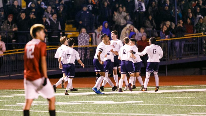 Stayton players celebrate their second goal of the match, the first during overtime, in a Class 4A state semifinal match against McLoughlin on Tuesday, Nov. 7, 2017, at Stayton High School. After two 10-minute periods of overtime, the Stayton Eagles defeated McLoughlin 2-1.