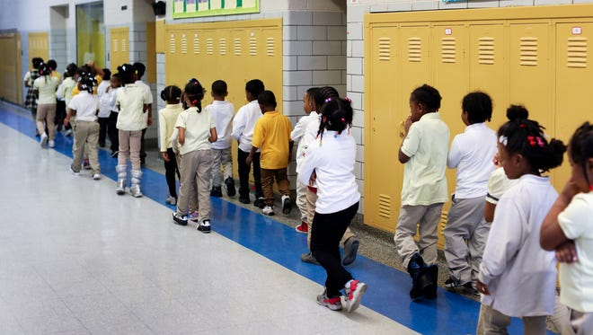 A kindergarten class of 38 students walks to the larger bathroom that has more stalls on the middle school side at Palmer Park Preparatory Academy in Detroit on Thursday, Feb. 1, 2018.