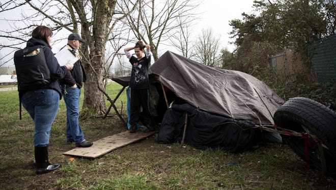 Clarissa, 28, right, answers survey questions from volunteers Carli Cohen and Jerry Steven during the Point-in-Time homeless count outside her tent where she was living with her fiancee and four dogs along Highway 22 earlier this year.