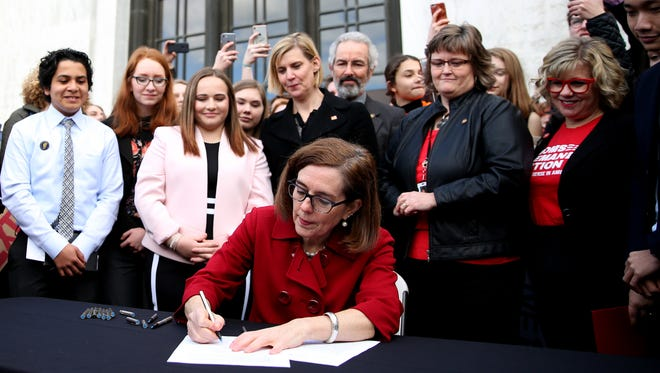 "Gov. Kate Brown signs HB 4145 at the Oregon State Capitol in Salem on Monday, March 5, 2018. The law expands the prohibition of owning a gun to people convicted of domestic violence, closing the ""intimate partner loophole"" and blocks people convicted of misdemeanor stalking from gun ownership."