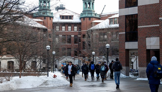 Students walk by the West Hall on U-M central campus in Ann Arbor in January 2018.