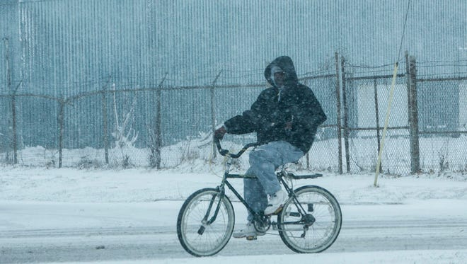 A man rides his bicycle through the snow in Muskegon, Mich., on Wednesday, April 4, 2018.  A spring storm dumped more than a foot of snow in parts of Michigan's northern Lower Peninsula and is blamed for creating hazardous road conditions.