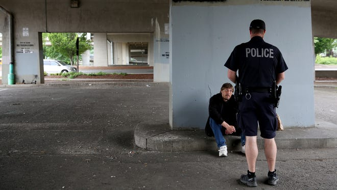 Salem Police Officer Andrew McFerron talks with Jonathan Jones, 49, who has been homeless in Salem for more than a year under the Center Street bridge in downtown Salem on Friday, May 25, 2018. Officer McFerron gave Jones a warning for trespassing after checking in with his parole officer.