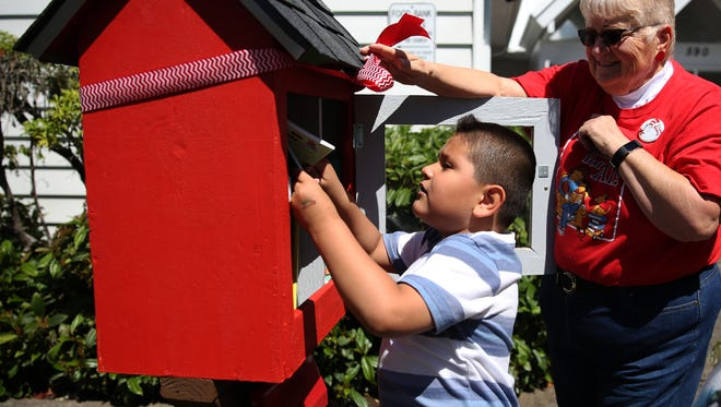 Axel Diaz, 5, of Salem, looks through available books as Kathy Martell watches during a grand opening for a Little Free Library at Trinity United Methodist Church near Four Corners Elementary School in Salem on Monday, June 11, 2018. Martell helped secure a grant so ten could be built around Salem for kids to trade books.
