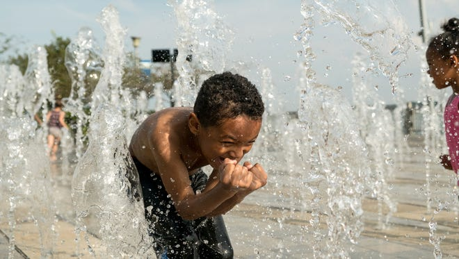In September 2017, Boston White of Detroit runs through the water being sprayed at a splash pad along the River Walk in downtown Detroit.