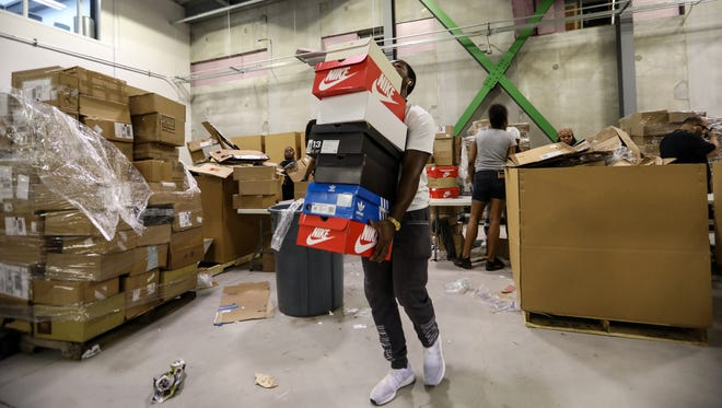 Tre Cadwell, 22, of Farmington carries sneakers to a station to be authenticated at the Stock X operations center in Detroit on Tuesday, July 3, 2018.
