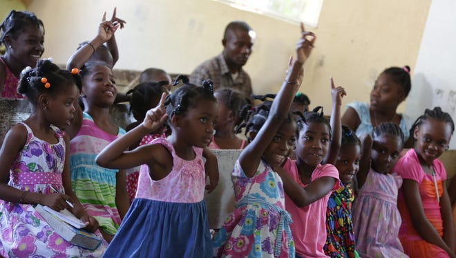 Children eagerly answer a question during a class at the Have Faith Haiti Mission in Port-au-Prince, where they are taught in English and French.