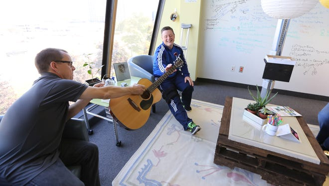 Jason Cooper, left, hands over his guitar to his boss Chief Financial Officer Tom Bomberski, who loves music and having work jam sessions at Billhighway in Troy.