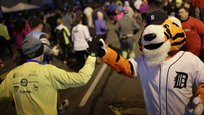 Detroit Tigers mascot Paws high fives runners as they leave the starting line during for the beginning of the 37th Annual Detroit Free Press/Talmer Bank Marathon in Detroit on Sunday, Oct. 19, 2014.