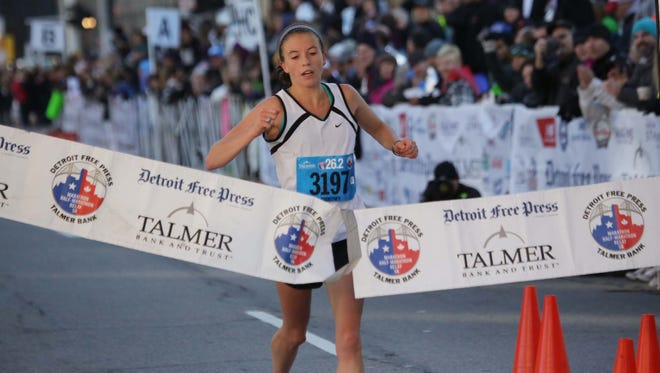 Courtney Brewis of Dearborn crosses the finish line to win the women's race in the 37th Detroit Free Press/Talmer Bank Marathon on Oct. 19, 2014.