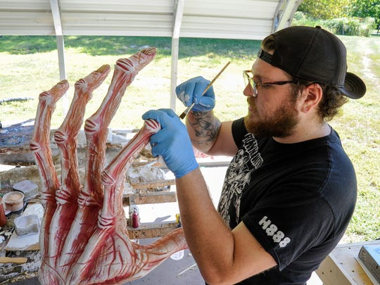 """Matt Dalrymple applies a shadow wash to some """"rotten candy hands"""" at the Gore Galore compound."""