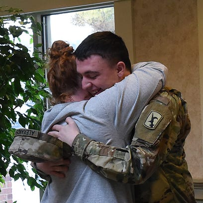 Army National Guard Pfc. Colton Alexander hugs his