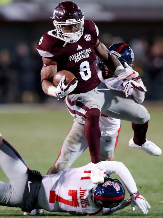 Mississippi State running back Kylin Hill (8) leaps over Mississippi defensive back Jalen Julius (7) on a 30-yard touchdown run during the second half of am NCAA college football game in Starkville, Miss., Thursday, Nov. 23, 2017. Mississippi won 31-28. (AP Photo/Rogelio V. Solis)