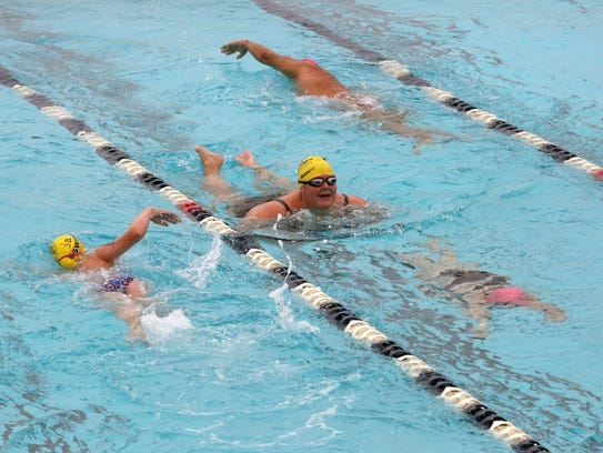 Swimmers swim laps in the pool during the 25th anniversary