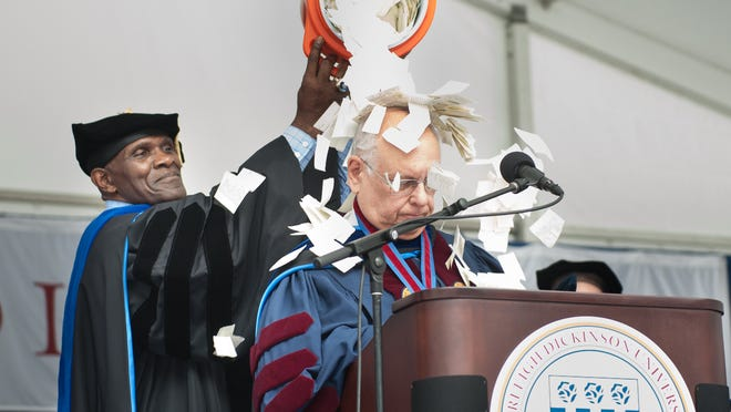 Keynote Speaker Harry Carson dumps a Gatorade bucket of confetti on Fairleigh Dickinson University President Sheldon Drucker's head at the conclusion of the school's graduation ceremony.