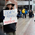 A man holds a sign outside the federal courthouse during the trial of Dzhokhar Tsarnaev in Boston.