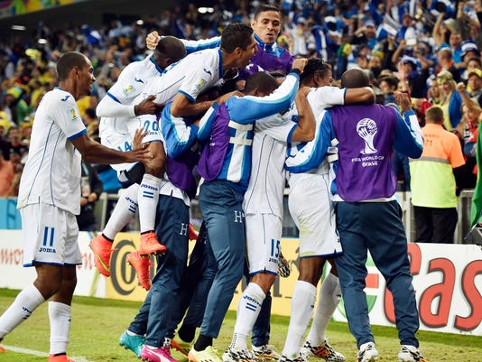 Honduras' Carlo Costly celebrates with teammates after scoring the opening goal during the group E World Cup soccer match between Honduras and Ecuador at the Arena da Baixada in Curitiba, Brazil, Friday, June 20, 2014.  (AP Photo/Martin Meissner)