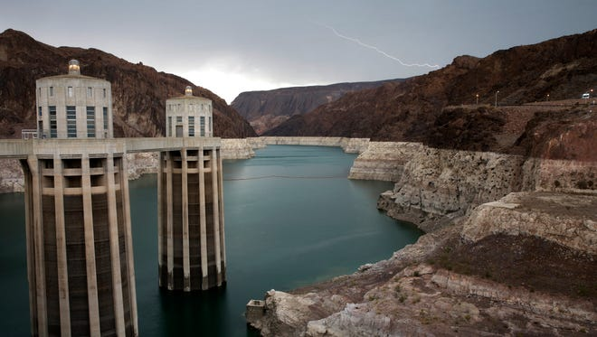 FILE - In this July 28, 2014 file photo, lightning strikes over Lake Mead near Hoover Dam at the Lake Mead National Recreation Area in Arizona. Federal water managers said Wednesday, May 9, 2018, that there is a better-than-even possibility that Mexico and the U.S. states of Arizona and Nevada will get less water from Lake Mead, a Colorado River reservoir, in 2020 because of a drought. (AP Photo/John Locher, File)