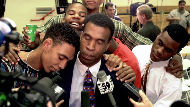Indiana's new interim head coach Mike Davis center pauses to share a warm moment with player Jared Jeffries left while talking to the media Tuesday Sept. 12 2000 at Assembly Hall in Bloomington Ind.  (AP Photo/South Bend Tribune Jim Rider)