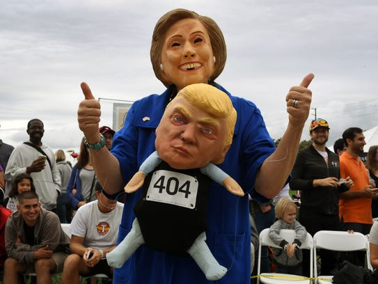 A woman wearing a Hillary Clinton mask carries a Republican
