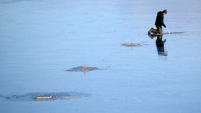 Ice fisherman Ralph Wendling prepares traps on the ice of Pontoosuc Lake in Pittsfield, Mass., on Jan. 1, 2015.