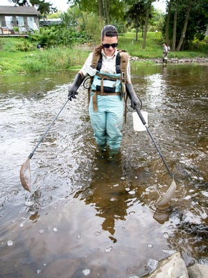 File - U.S. Fish and Wildlife Service Biologist Rebecca Phillips and Biological Service Technician Nick Rewald use wire mesh paddles to run an electric current into the sediment of the East Twin River out of Mishicot to search for invasive sea lamprey larvae in 2016.