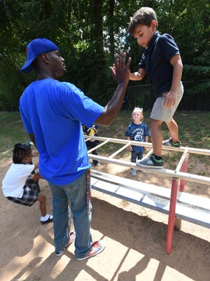 Brandon Lacey gives a student a high five after the young climber was able to balance a top the playground equipment.