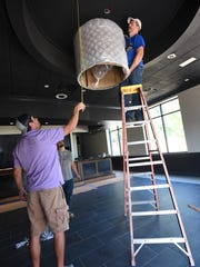 Crews work to hang a new chandelier in the bar of the