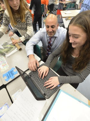 Karolina  Kedzierska (left) looks over the shoulder of fifth grade teacher Brad Bertani as he checks out Maddie Fosko's work. Students at Riverview Elementary School in Denville are taking part in a global program this week that kicked off Dec. 5.
