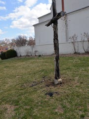 A burnt cross in front of the Marquis Memorial United