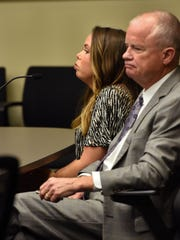 Kelsey McCarter and her attorney Doug Trant sit in