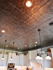 The kitchen is adorned with a stamped tin ceiling.