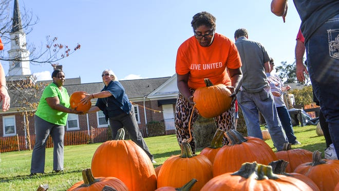 Cleervette Leslie, right, helps unload over 2,600 pumpkins from New Mexico for the Trinity United Methodist Church Pumpkin Patch in Anderson on Wednesday. Trinity selected recipients of this year's funds for Anderson Interfaith Ministries, Boy Scouts, Cancer Association of Anderson, Costa Rica Missions, Family Promise, Offer's Christian Fellowship, Parkinson's Association of Anderson, and the Weekend SnackPack program.