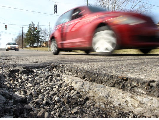 A car rolls past a pothole on Daly Road in Finneytown,