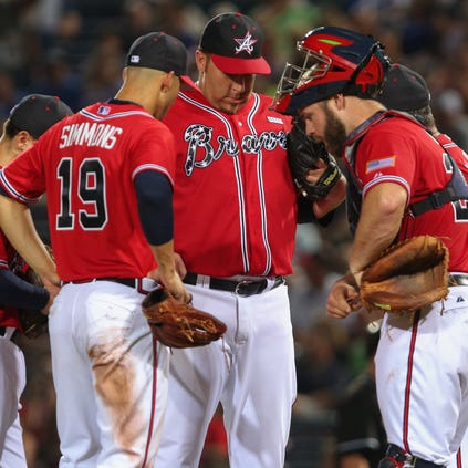 Aaron Harang #34 of the Atlanta Braves (center) talks with Andrelton Simmons #19 and Evan Gattis #24 against the Miami Marlins